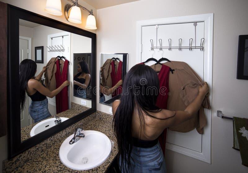 Γυναίκα που προσπαθεί στα ενδύματα που εξετάζουν τον καθρέφτη στο λουτρό στοκ φωτογραφίες με δικαίωμα ελεύθερης χρήσης