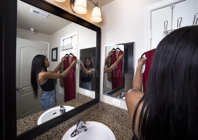 Γυναίκα που προσπαθεί στα ενδύματα που εξετάζουν τον καθρέφτη στο λουτρό στοκ φωτογραφία με δικαίωμα ελεύθερης χρήσης