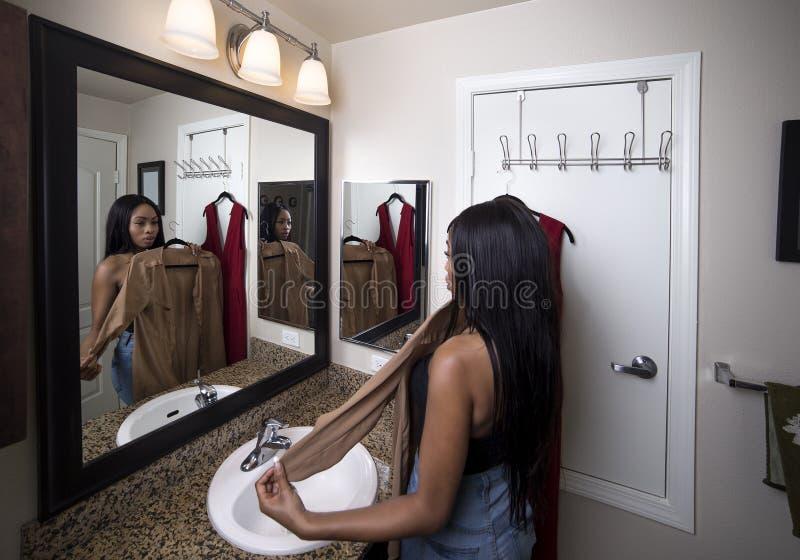 Γυναίκα που προσπαθεί στα ενδύματα που εξετάζουν τον καθρέφτη στο λουτρό στοκ εικόνες