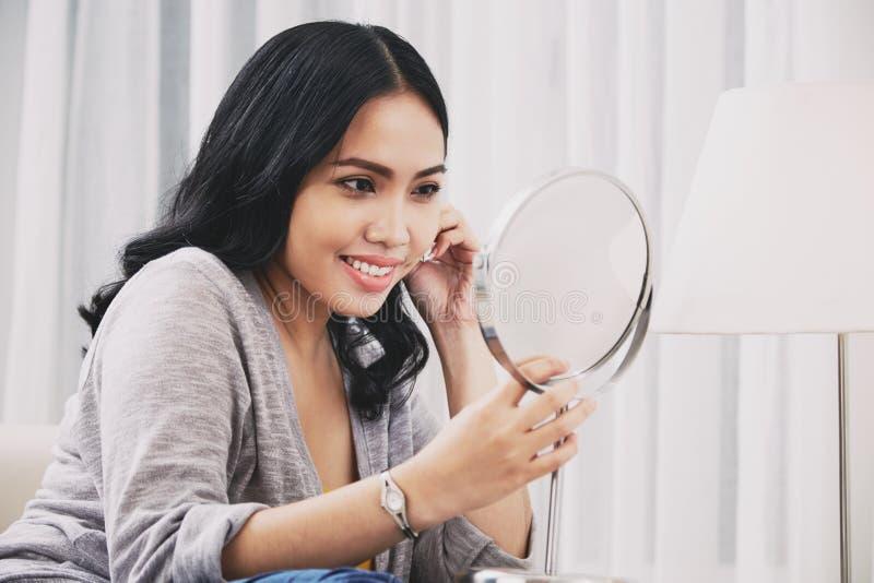 Γυναίκα που προσπαθεί στο σκουλαρίκι στοκ εικόνα