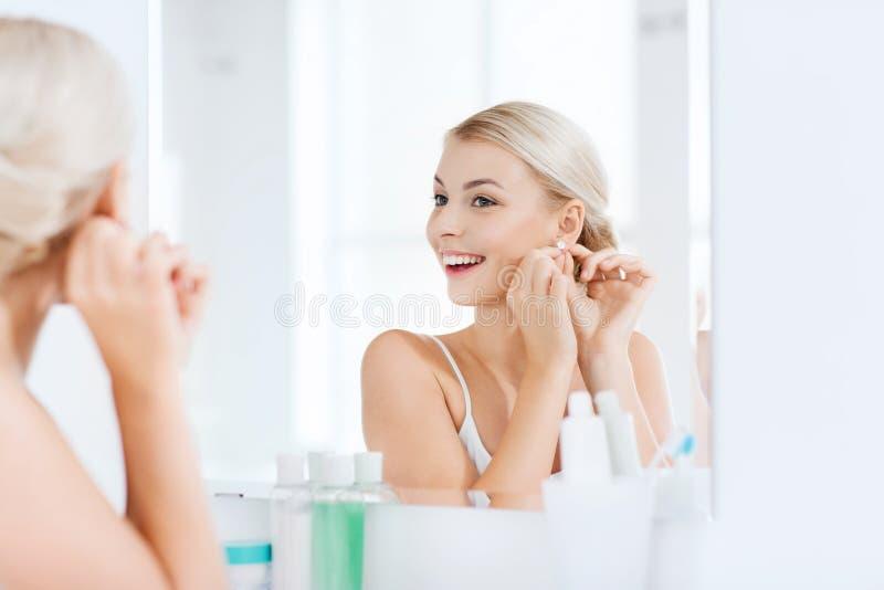 Γυναίκα που προσπαθεί στο σκουλαρίκι που εξετάζει τον καθρέφτη λουτρών στοκ εικόνα με δικαίωμα ελεύθερης χρήσης