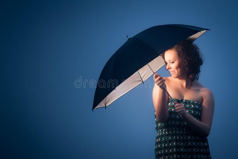 Γυναίκα που προστατεύεται χαρούμενη από μια ομπρέλα στοκ φωτογραφία