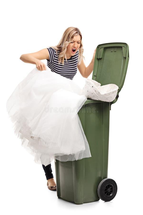 Γυναίκα που ρίχνει το γαμήλιο φόρεμά της στα απορρίμματα στοκ εικόνα με δικαίωμα ελεύθερης χρήσης