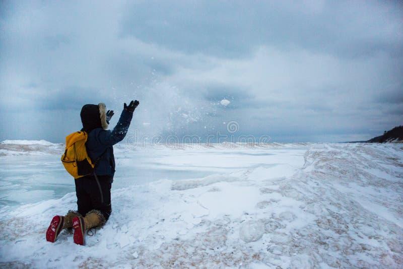 Γυναίκα που ρίχνει το χιόνι γονατίζοντας στο παγωμένο κύμα στοκ εικόνες