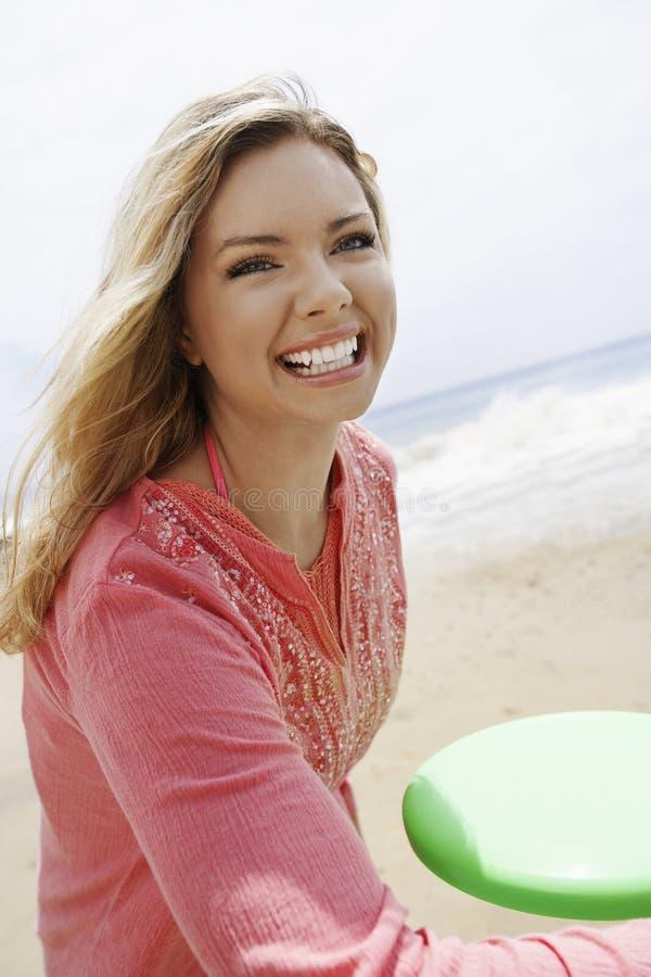 Γυναίκα που ρίχνει Frisbee στην παραλία στοκ εικόνα με δικαίωμα ελεύθερης χρήσης