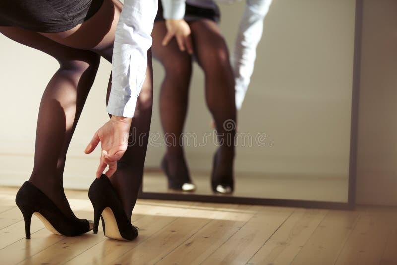 Γυναίκα που ρυθμίζει τα υψηλά τακούνια στοκ εικόνες