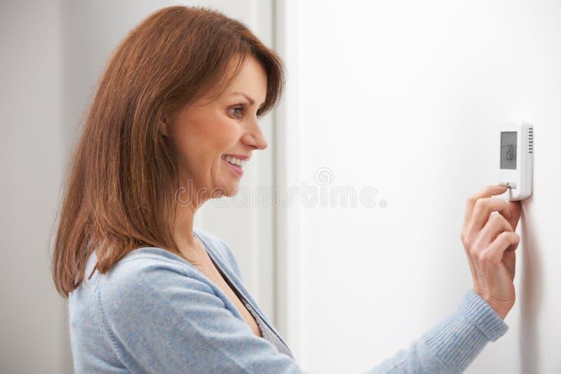 Γυναίκα που ρυθμίζει τον ψηφιακό έλεγχο θερμοστατών κεντρικής θέρμανσης στοκ εικόνα με δικαίωμα ελεύθερης χρήσης