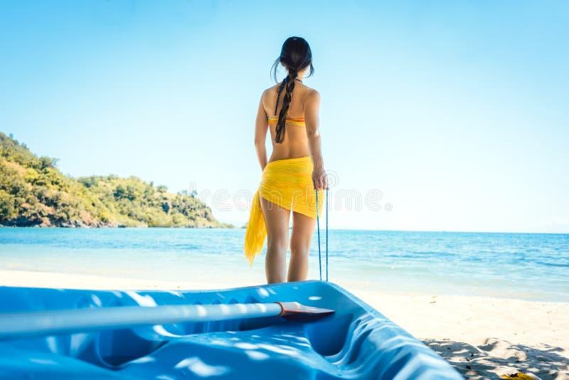 Γυναίκα που σέρνει τη βάρκα της στο νερό στην παραλία στοκ φωτογραφίες με δικαίωμα ελεύθερης χρήσης