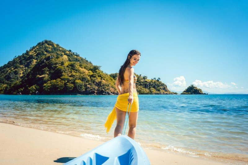 Γυναίκα που σέρνει τη βάρκα της στο νερό στην παραλία στοκ φωτογραφία με δικαίωμα ελεύθερης χρήσης