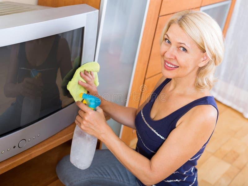 Γυναίκα που σκουπίζει τη TV σκόνης στοκ εικόνες