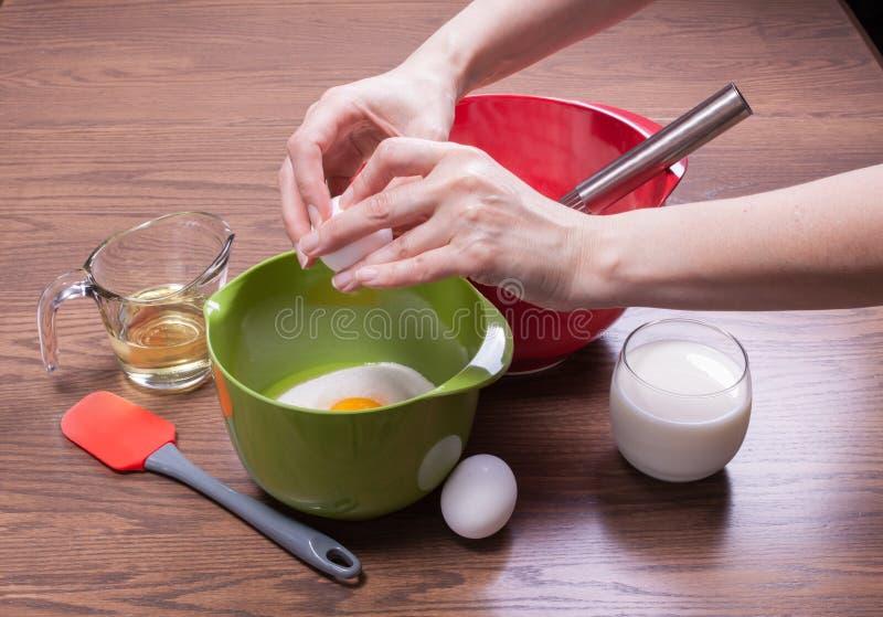 Γυναίκα που σπάει αυγά σε ένα μπολ για να μαγειρέψει μια τούρτα στοκ φωτογραφία