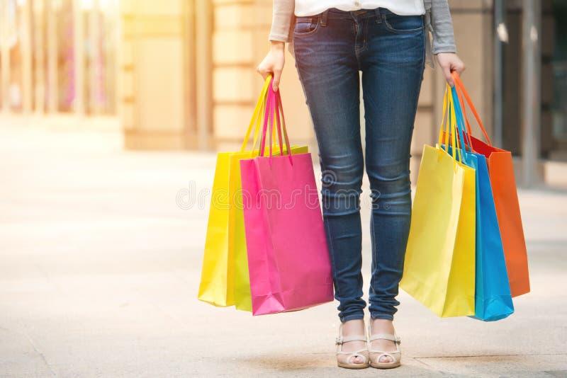 Γυναίκα που στέκεται και που κρατά τις τσάντες εγγράφου χρώματος αγορών στοκ φωτογραφία