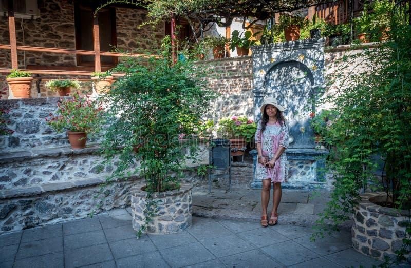 Γυναίκα που στέκεται και που χαμογελά μπροστά από τον τοίχο πηγών και πετρών στοκ φωτογραφία