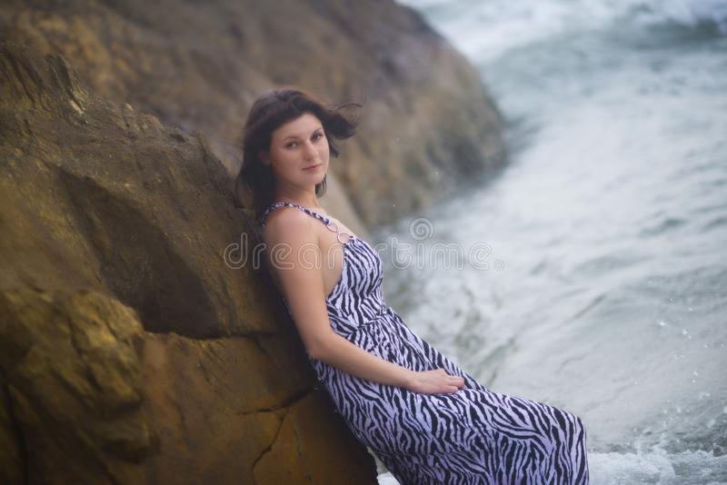 Γυναίκα που στέκεται κοντά σε έναν βράχο στο υπόβαθρο του ωκεανού το καλοκαίρι στοκ φωτογραφίες με δικαίωμα ελεύθερης χρήσης