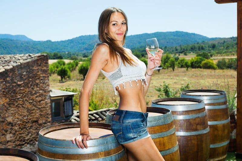 Γυναίκα που στέκεται μεταξύ των ξύλων κρασιού με το ποτήρι του λαμπιρίζοντας κρασιού στοκ φωτογραφίες