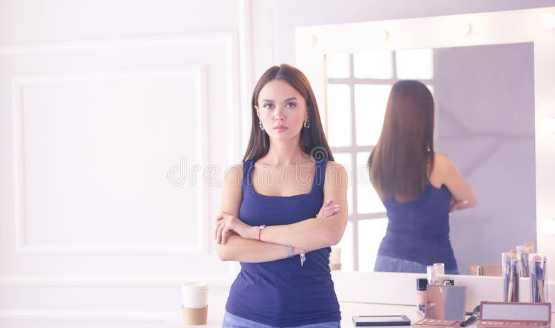 Γυναίκα που στέκεται με τα χέρια που διπλώνονται στο σαλόνι της στοκ φωτογραφία με δικαίωμα ελεύθερης χρήσης