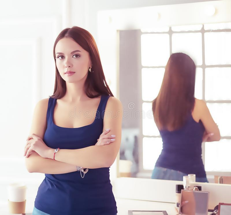 Γυναίκα που στέκεται με τα χέρια που διπλώνονται στο σαλόνι της στοκ φωτογραφία