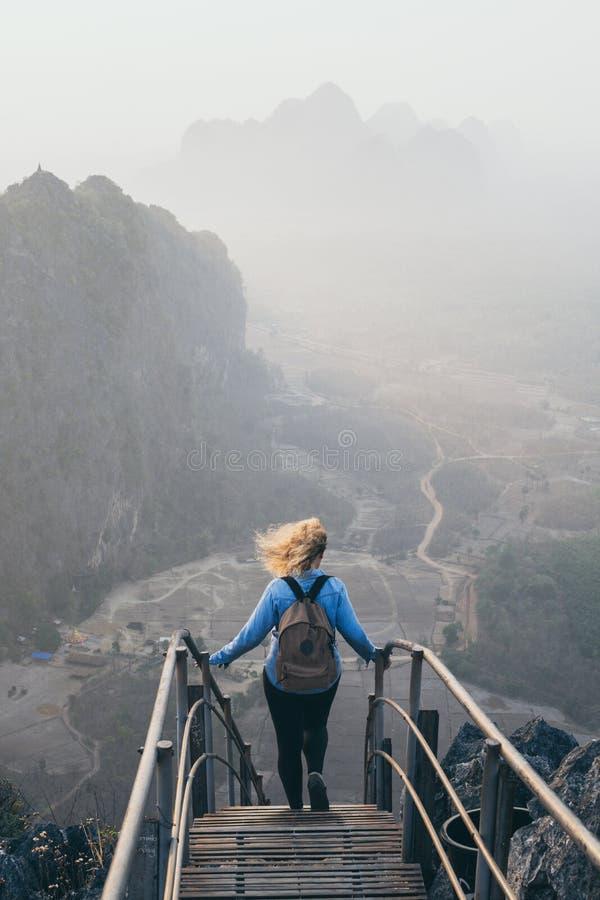 Γυναίκα που στέκεται στην αιχμή βουνών με τα σκαλοπάτια που πηγαίνουν κάτω κατά τη διάρκεια του ομιχλώδους πρωινού ανατολής hpa-, στοκ εικόνα