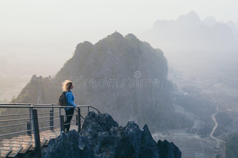 Γυναίκα που στέκεται στην αιχμή βουνών με τα σκαλοπάτια που πηγαίνουν κάτω κατά τη διάρκεια του ομιχλώδους πρωινού ανατολής hpa-, στοκ φωτογραφίες