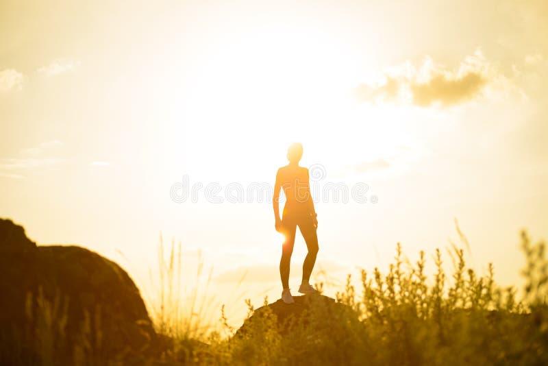 Γυναίκα που στέκεται στην κορυφή του βράχου ενάντια στο φωτεινό ηλιοβασίλεμα r στοκ φωτογραφία με δικαίωμα ελεύθερης χρήσης