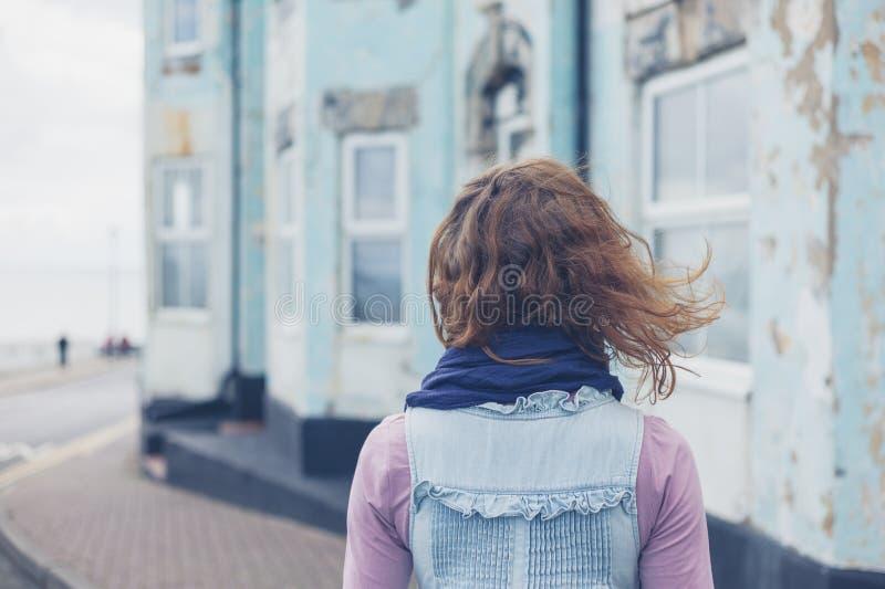 Γυναίκα που στέκεται στην οδό έξω από το μπλε σπίτι στοκ φωτογραφία