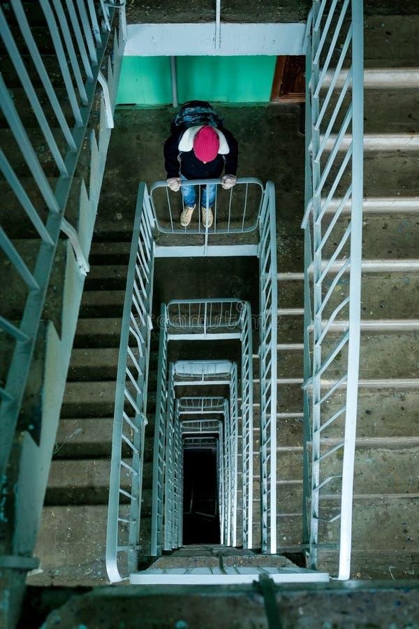 Γυναίκα που στέκεται στη shabby έκταση σκαλών στο παλαιό σπίτι και που κοιτάζει κάτω στοκ εικόνες