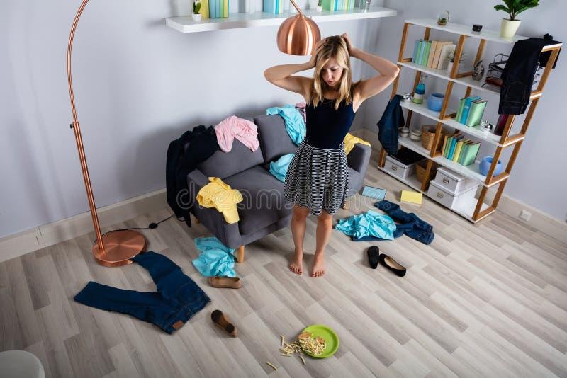 Γυναίκα που στέκεται στο ακατάστατο δωμάτιο στοκ εικόνα με δικαίωμα ελεύθερης χρήσης