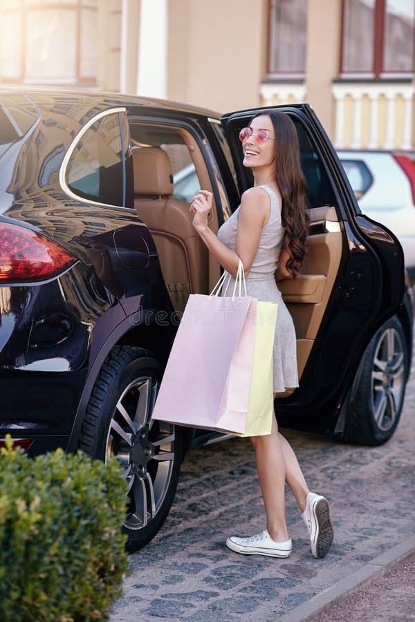 Γυναίκα που στέκεται στο αυτοκίνητο με τις τσάντες αγορών στοκ εικόνες