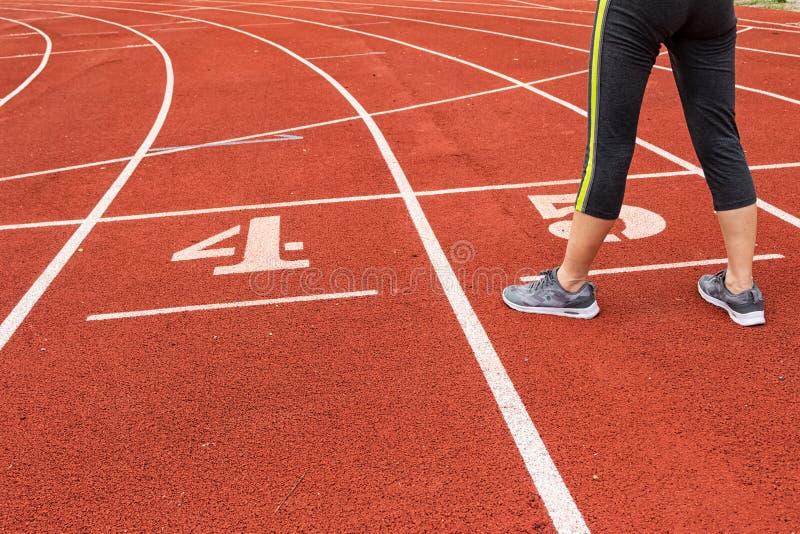 Γυναίκα που στέκεται στο τρέξιμο της διαδρομής στοκ εικόνα με δικαίωμα ελεύθερης χρήσης