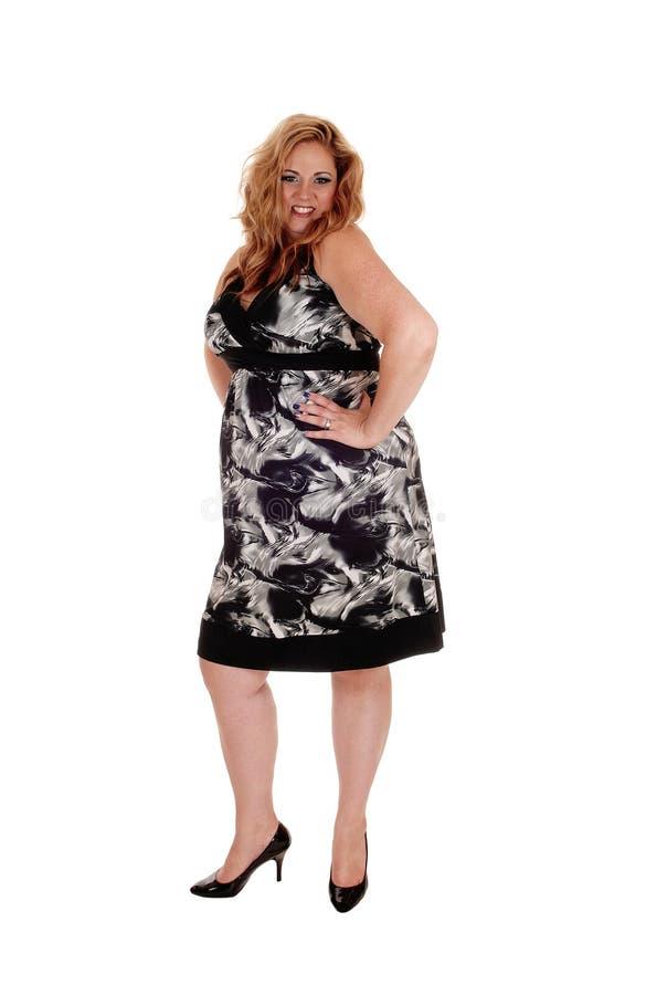 Γυναίκα που στέκεται στο φόρεμα, χαμόγελο στοκ εικόνες