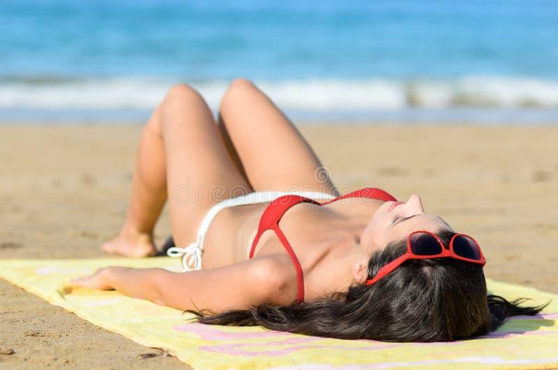 Γυναίκα που στηρίζεται και που κάνει ηλιοθεραπεία στην παραλία στοκ φωτογραφία