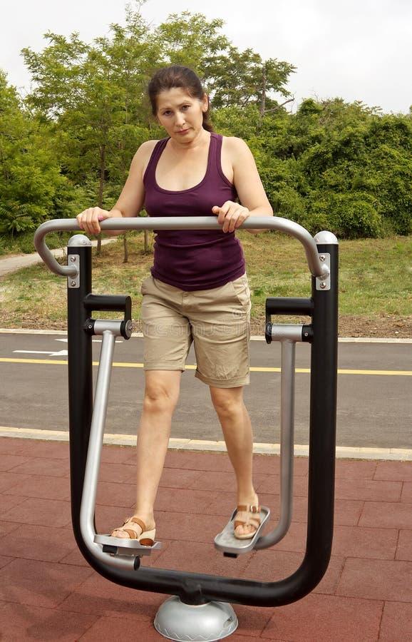 Γυναίκα που στηρίζεται μετά από τις ασκήσεις υπαίθρια στοκ εικόνα