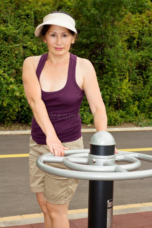 Γυναίκα που στηρίζεται μετά από τις ασκήσεις υπαίθρια στοκ εικόνες