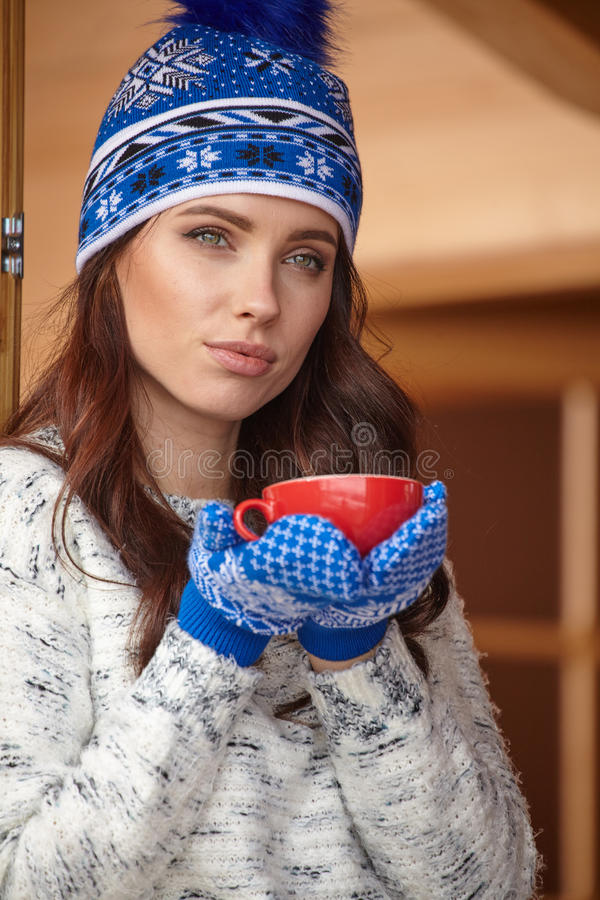 Γυναίκα που στηρίζεται μετά από τον αθλητισμό ενός χειμώνα στο πεζούλι του σπιτιού στοκ εικόνα
