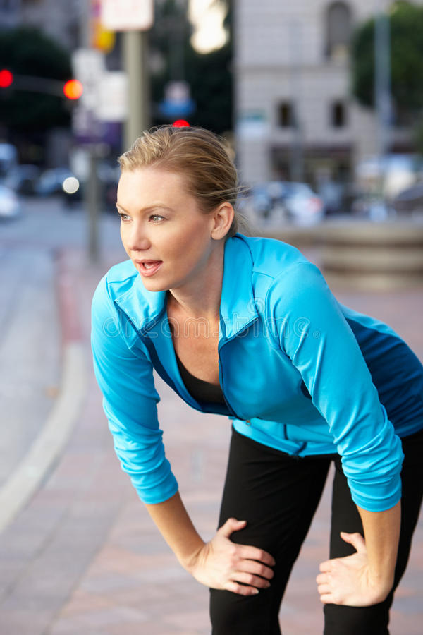 Γυναίκα που στηρίζεται ταυτόχρονα τρέχοντας κατά μήκος της αστικής οδού στοκ φωτογραφίες με δικαίωμα ελεύθερης χρήσης
