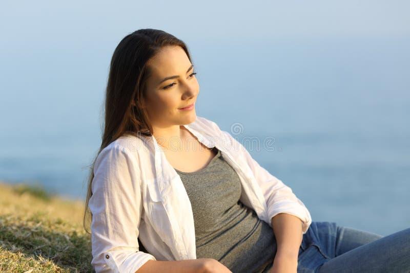 Γυναίκα που συλλογίζεται στη χλόη σε μια παραλία στοκ εικόνες