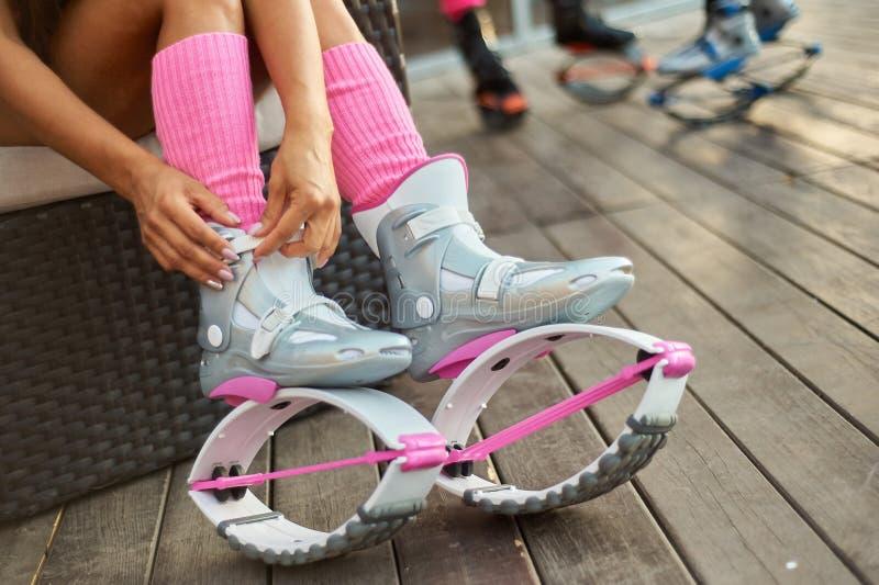 Γυναίκα που τίθεται στις μπότες αλμάτων kangoo πριν από την υπαίθρια ικανότητα workout στοκ φωτογραφίες με δικαίωμα ελεύθερης χρήσης