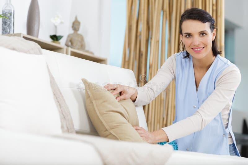 Γυναίκα που τακτοποιεί τον καναπέ στοκ φωτογραφία