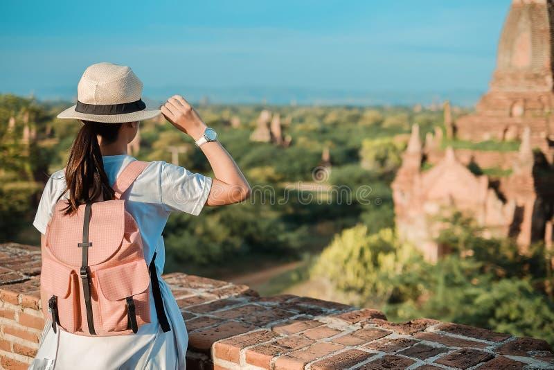 Γυναίκα που ταξιδεύει backpacker με το καπέλο, ασιατικός ταξιδιώτης που στέκεται στην παγόδα και που φαίνεται όμορφοι αρχαίοι ναο στοκ εικόνες