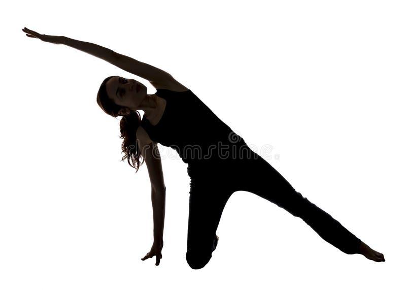 Γυναίκα που τεντώνει το δευτερεύον σώμα της στη γιόγκα, σκιαγραφία στοκ εικόνες