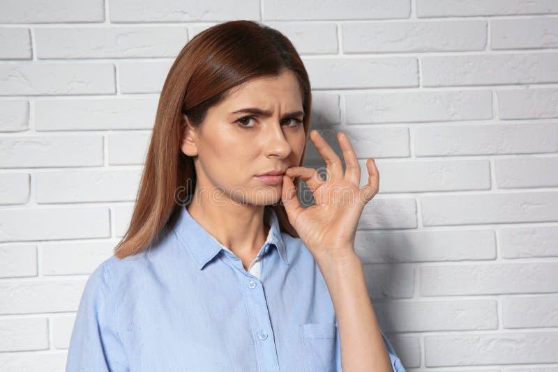 Γυναίκα που το στόμα της κοντά στο τουβλότοιχο Χρησιμοποίηση της γλώσσας σημαδιών στοκ εικόνα με δικαίωμα ελεύθερης χρήσης