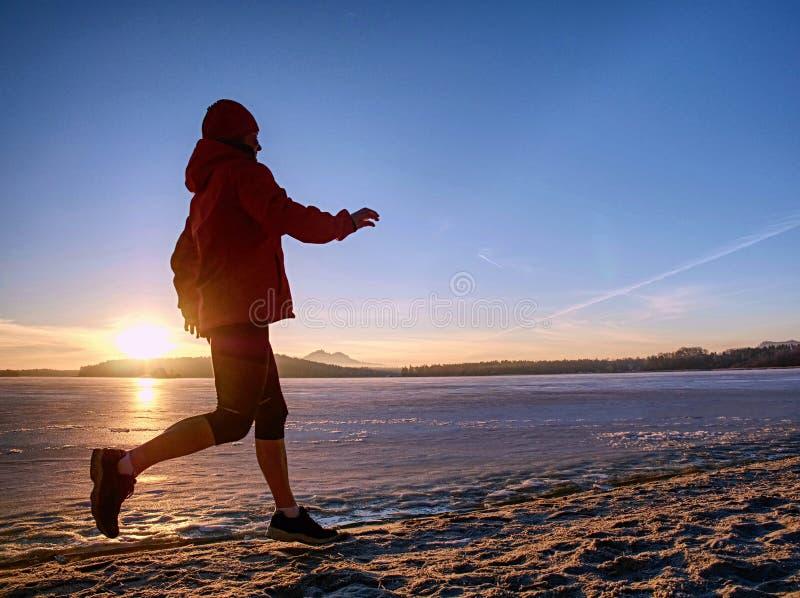 Γυναίκα που τρέχει κατά μήκος της ακτής μιας παγωμένης λίμνης τη χειμερινή άνοιξη στοκ εικόνες
