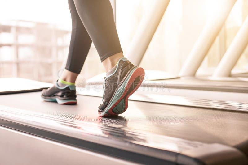 Γυναίκα που τρέχει σε μια γυμναστική σε μια treadmill έννοια για την άσκηση, την ικανότητα και τον υγιή τρόπο ζωής στοκ φωτογραφία