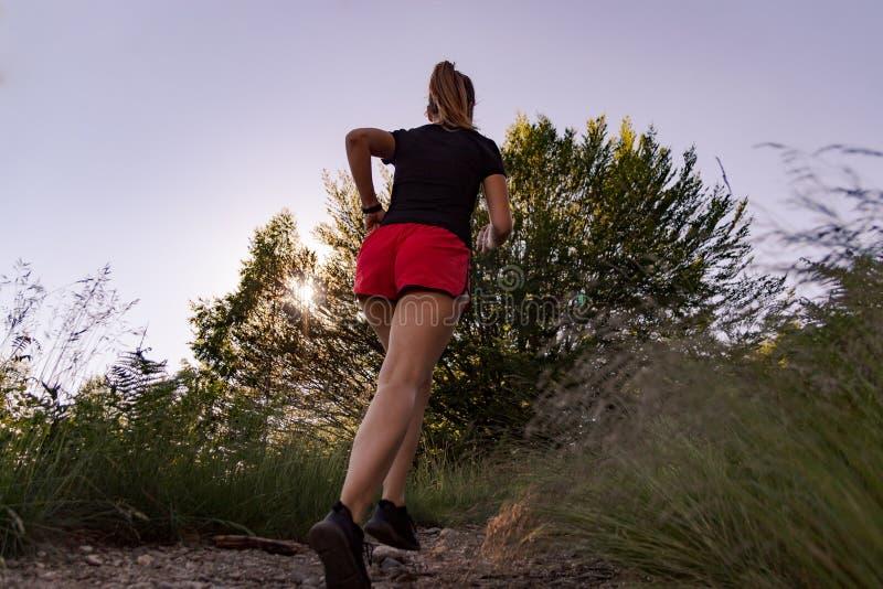 Γυναίκα που τρέχει στα βουνά στο ηλιοβασίλεμα στοκ εικόνα