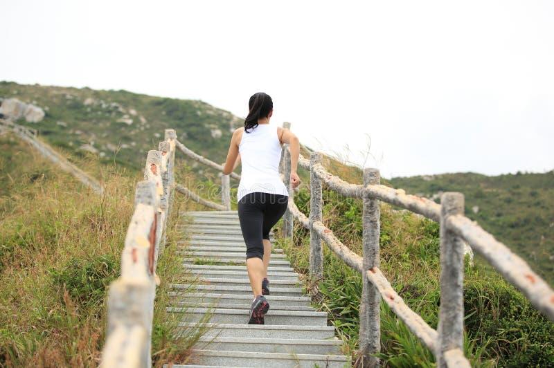 Γυναίκα που τρέχει στα σκαλοπάτια βουνών στοκ εικόνα