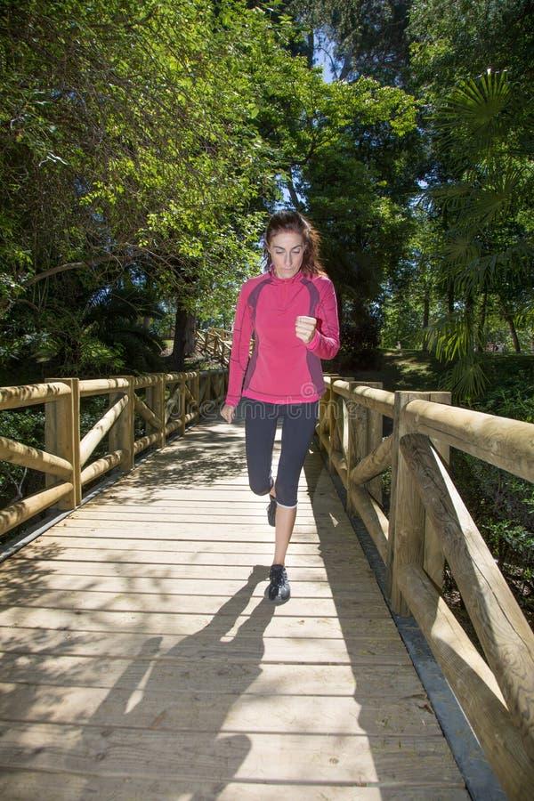 Γυναίκα που τρέχει στην ξύλινη γέφυρα για πεζούς στο πάρκο στοκ εικόνες με δικαίωμα ελεύθερης χρήσης