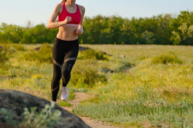 Γυναίκα που τρέχει στο ίχνος βουνών το καυτό θερινό βράδυ Αθλητισμός και ενεργός τρόπος ζωής στοκ φωτογραφία με δικαίωμα ελεύθερης χρήσης