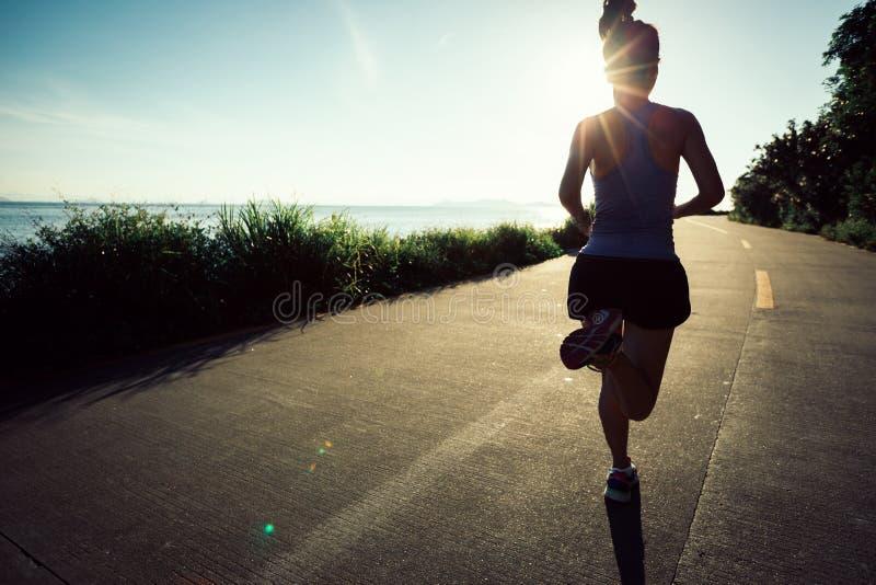 Γυναίκα που τρέχει στο ίχνος παραλιών στοκ εικόνες