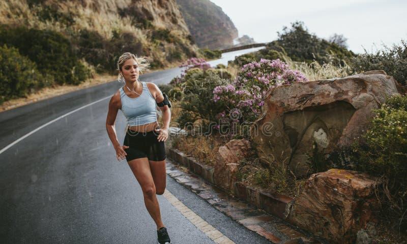 Γυναίκα που τρέχει στο δρόμο γύρω από τα βουνά στοκ φωτογραφία με δικαίωμα ελεύθερης χρήσης