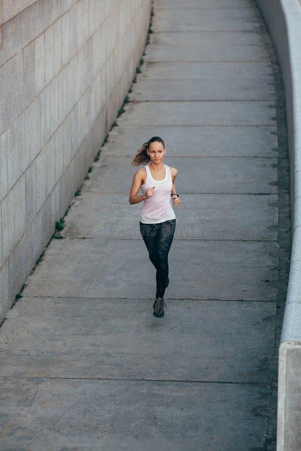 Γυναίκα που τρέχει στο συγκεκριμένο αστικό scape στοκ εικόνες με δικαίωμα ελεύθερης χρήσης
